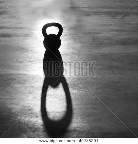 Kettlebell weight backlight and shadow on the gym floor