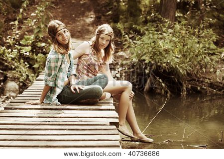 Young girls sitting on the wooden bridge