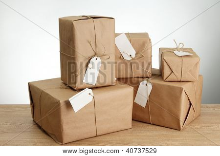 parcels boxes with kraft paper, on wooden table on grey background