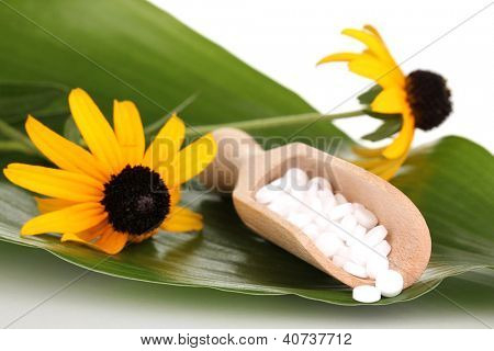 homeopathic tablets and flowers on green leaf isolated on white