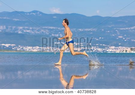 Man run across the beach in blue bathing suit