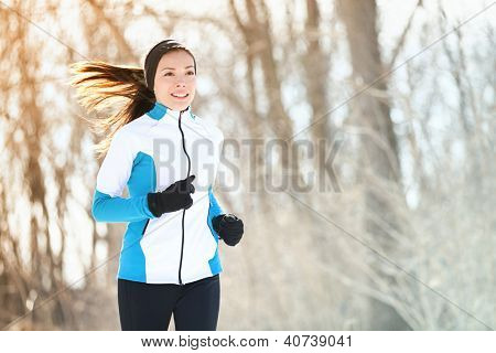 Running sport woman. Female runner jogging in cold winter forest wearing warm sporty running clothing and gloves. Beautiful fit Asian / Caucasian female fitness model.