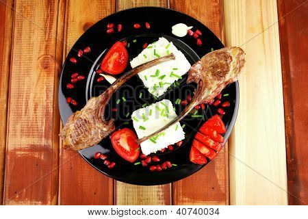 meat food: ribs on black with rice garnish and tomatoes on black on wood
