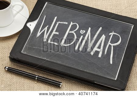webinar word - white chalk handwriting on old slate blackboard on a screen of a digital tablet computer with a coffee cup and stylus pen