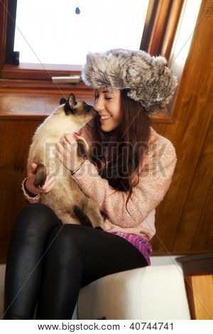Woman in a cozy attic with her cat