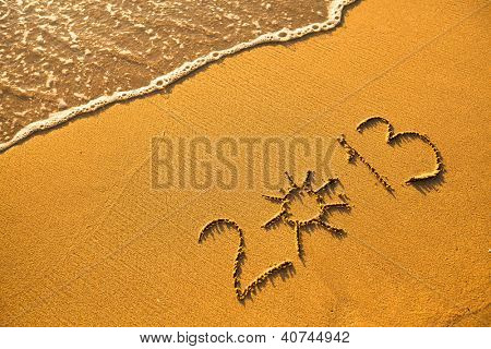 Abstract picture: 2013 written in sand on beach texture (soft wave of the sea)