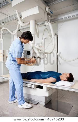 Full length of mid adult radiologist technician setting up machine to take patient's x-ray