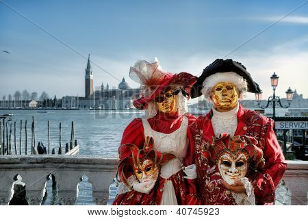 VENICE - MARCH 04: Participants in red costumes and golden masks standing on bridge against Grand Canal and San Giorgio Maggiore church during traditional carnival in Venice, Italy on March 04, 2011.