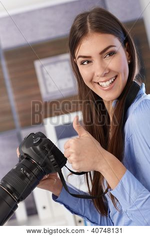 Pretty photographer girl holding camera, laughing, giving thumb up.