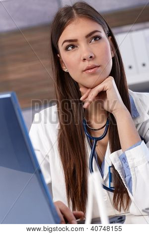Portrait of pretty young doctor sitting in office with laptop computer.