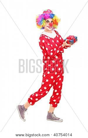 Full length portrait of a male clown with joyful expression on his face holding a gift isolated on white background