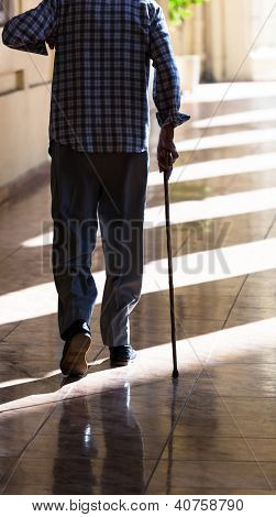an old man with a cane on the sidewalk