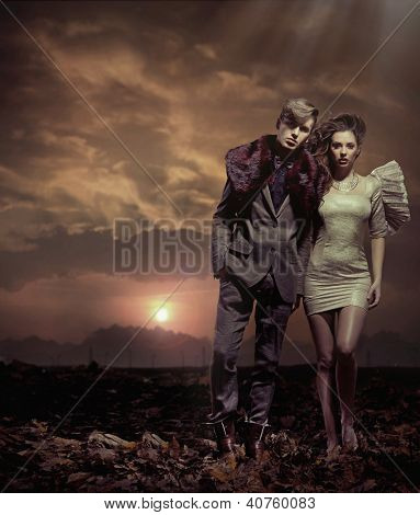 Young couple over sunset background