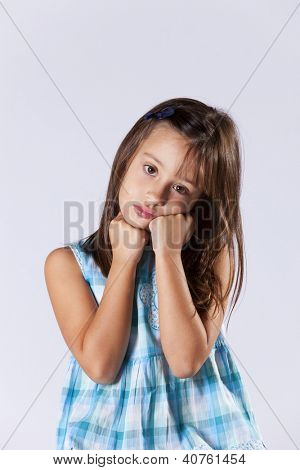 Upset expression from a little girl (isolated on gray)