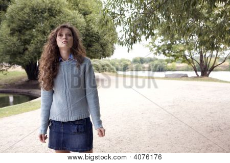 Young Woman Walking In A Park.