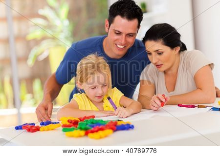 happy parents watching little daughter drawing picture
