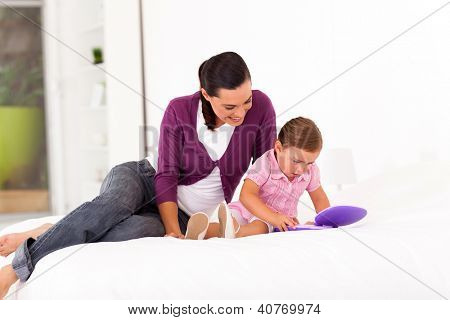 little girl playing toy laptop on bed with mother at home