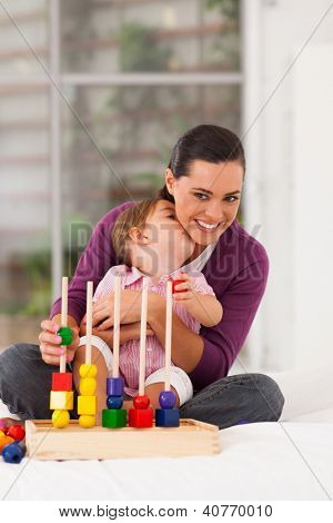 cute daughter kissing mother while playing with toy