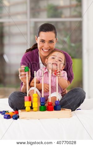 happy little girl playing wooden toy with mother at home