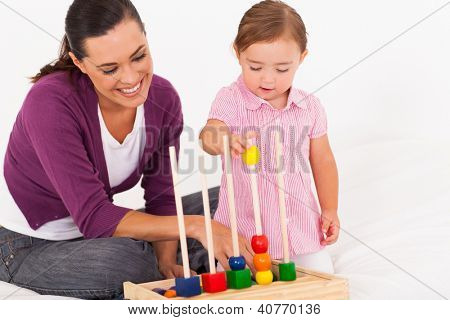 little daughter playing educational toy with mother