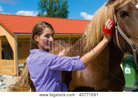 Young woman in the stable with horse and caring