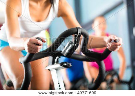 Jovens - grupo de mulheres e homens - fazendo esporte girando no ginásio de fitness