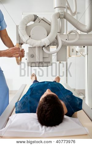 Male technician setting up machine to take patient's x-ray
