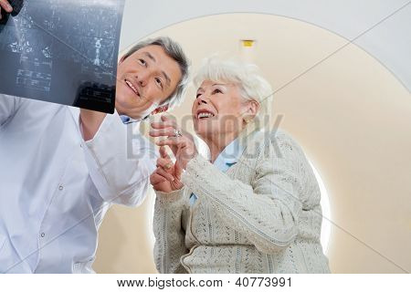 Mature male radiologist with an elderly female patient looking at x-ray