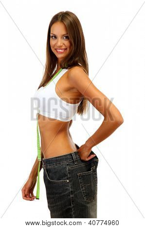 beautiful young woman with big jeans and measuring tape, isolated on white