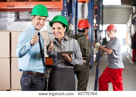 Portrait of supervisors with digital tablet gesturing thumbs up with workers in background