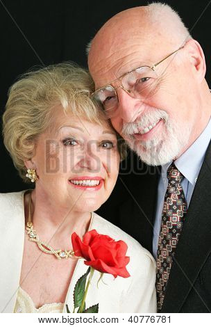 Elegant senior couple dressed up in their finery, and holding a Valentines Day rose.