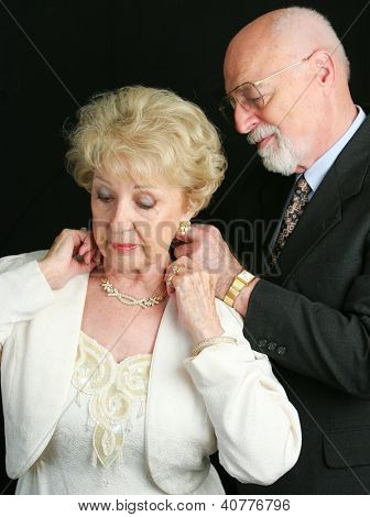 Senior man helping his wife put on a beautiful diamond necklace he has given her as a gift.