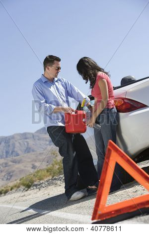 Couple refueling car