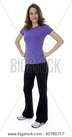 Woman dressed in sportswear with hands on hips, standing on white background.