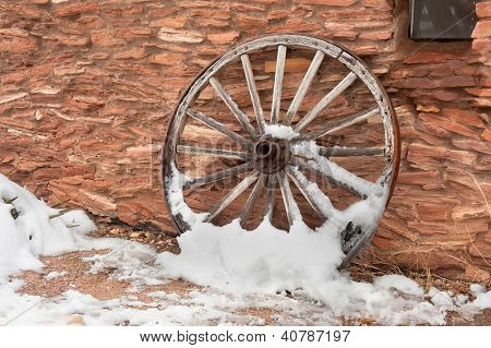 An old, antique wagon wheel covered in snow rests against a ranch facility wall.