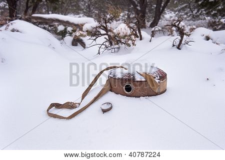 An empty vintage hiking and camping canteen lying in the snow in a remote part of the desert during a snowy winter.