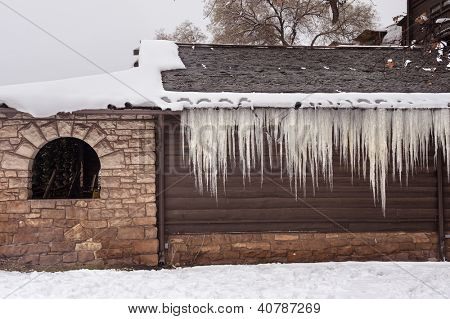 A mountain chalet lodge exterior covered in snow and icicles shows an idyllic winter vacation destination.