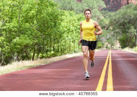 Runner man running on road training sprint for marathon run. Sporty fit caucasian male fitness sport model working out outside in full length.