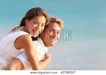Multiracial people: Happy couple piggybacking cheerful on beach during summer holidays vacation.