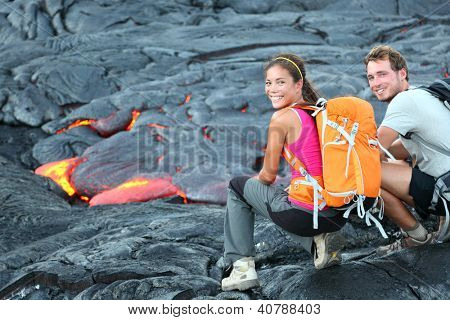 Hawaii lava tourist on hike. Tourists hiking near flowing lava from Kilauea volcano around Hawaii volcanoes national park, USA. Multiethnic couple.