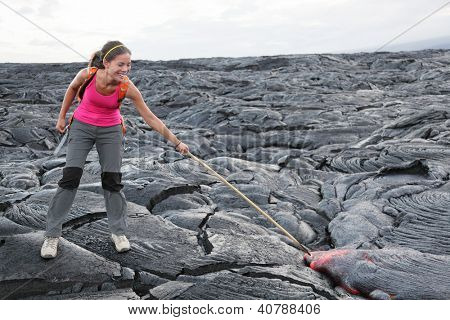 Hawaii Big Island lava tourist on volcano poking stick in red hot moving lava. flowing lava from Kilauea volcano around Hawaii volcanoes national park, USA. Young asian woman hiker.