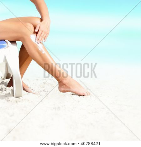 Sunscreen / suntan lotion. Woman putting sun screen lotion on sexy legs on beautiful beach on summer holidays.