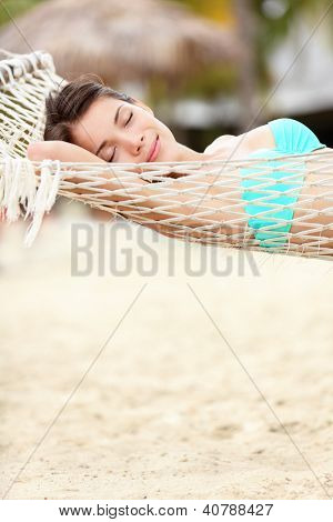 Beach lifestyle woman relaxing in hammock on tropical holidays vacation. Multiethnic Asian Chinese / Caucasian model in bikini on Varadero Beach, Cuba, Caribbean