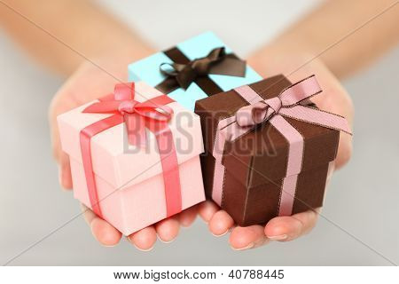 Cropped view image of a woman holding three colourful Christmas gifts with decorative ribbons and bows in the palms of her her hands, can also be used for anniversary, birthday or other celebration