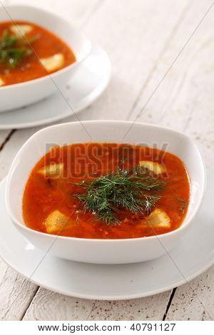 Image of two bowls of hot red soup isolated on white wooden table