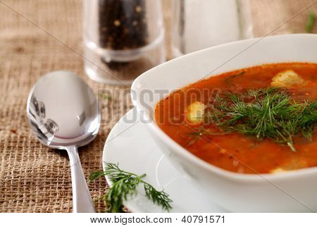 Image of bowl of hot red soup served with the salt, pepper and spoon on a beige tablecloth