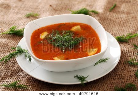 Image of bowl of hot red soup served with parsley on a beige tablecloth