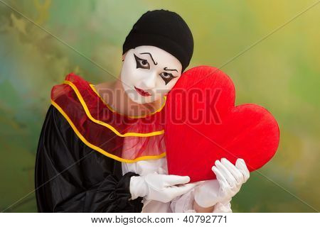 Sad Valentine Pierrot holding a red heart