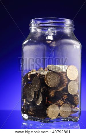 Glod coins in jar on blue background