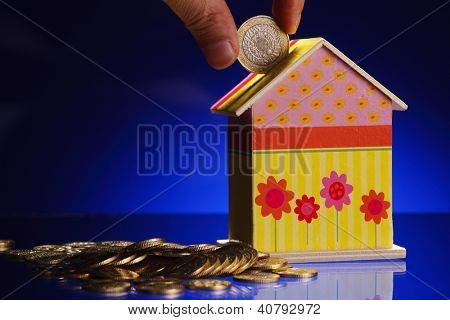 hand putting a coin into a house shaped money box